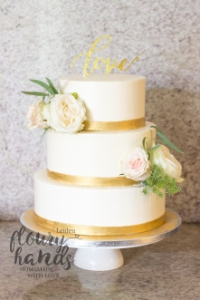 elegant white wedding cake with golden ribbon and real flowers