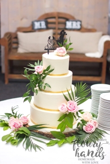 white elegant wedding cake with real flowers and golden ribbon for tier