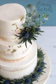 semi-naked wedding cake with thistel and eucalyptus and gold